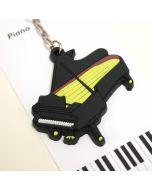 Llavero de goma con forma de piano de cola negro y amarillo